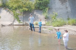 """— Shane and Jamie Baker of Thornton watched their eight-year-old son, Jacob, and 12-year-old daughter, Trinity, fish the """"Bill Doug Hole"""" in North Fork of the Kentucky River recently. The spot is located near River Park. Elsewhere in this week's issue, Mountain Eagle fishing columnist Greg """"Gabby"""" Caudill writes about the rewards of a family fishing trip. His column appears on Page 10. (Photo by Sally Barto)"""