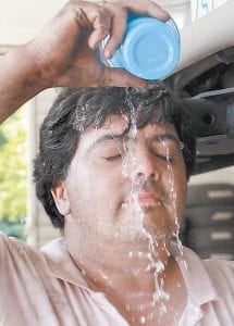 Victor Leguizamon poured water over his head to cool off after fixing a customer's transmission at a shop in Raleigh, N.C., where like in Kentucky, temperatures exceeded 100 degrees. (AP Photo/The News & Observer)