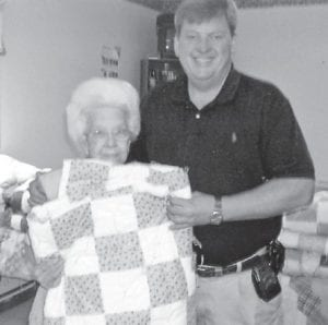 Letcher County Judge/Executive Jim Ward and Mabel Absher display the quilt which she gave to Ward.