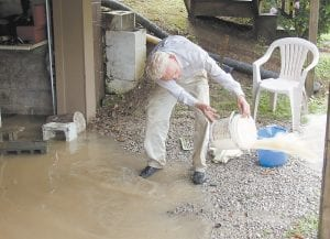 Curt Caudill used a bucket to remove water from his basement garage after heavy rains hit Redfox, near the Letcher- Knott county line, recently. While much of the rest of the nation is experiencing a damaging drought, Letcher and neighboring counties have been receiving more rainfall than usual for this time of year. (Photo by Ben Gish)