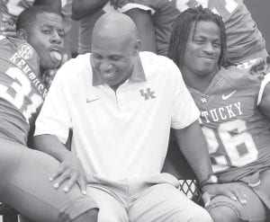 Kentucky football head coach Joker Phillips, center, smiled as players Mikie Benton, left, and CoShik Williams made faces during NCAA college football media day at Commonwealth Stadium in Lexington. (AP Photo)