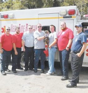 Pictured left to right are Mike Baker, Cory Baker, Scott Collins, Spanky Bolling (holding the owl), Shane Childers, Charles Polly and Brian Chapman in front of the ambulance getting ready to transport the owl to Whitesburg.