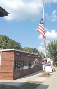 Visitors read the names on the monument while the flag remained at half-staff in honor of late veterans.
