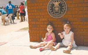 Cousins Lily McDaniel and Aaliyah Abdoo found a quiet spot beside the end of the monument after their great-grandfather Herbert Ray Short, a World War II vet, took part in the unveiling ceremonies.