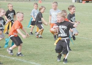 — Paxton Hammonds, a kindergarten student at West Whitesburg Elementary School, carried the ball during a flag football game last week at the old Whitesburg High School field. About 30 kindergarten and first-grade students are playing flag football in the first year of the program at WWES. (Photo by Sally Barto)