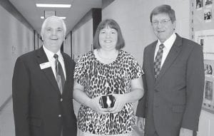 """Judy Adams of Jeremiah displays a watch presented to her in honor of her 25 years of service at Hazard Community and Technical College. Most of her years were spent in the Upward Bound program, which ended August 31. She is shown with Doug Fraley, vice president of Student Services (on left) and HCTC President Dr. Steve Greiner. She says she has enjoyed her time at HCTC. """"I like that everyone works as a team. It's like a big family. Everyone is supportive,"""" Adams said, adding, """"I've really enjoyed the high school and college students I've worked with here."""""""