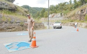 Wade Quillen, an employee with Letcher County Public Schools, spray painted Cougar paw prints with the help of a stencil last week on the road leading to Letcher County Central High School at Ermine. Cougar paw prints were painted on the road when the school first opened, but had since faded away. The new prints are in place in time for the Letcher County Central football team's home opener Friday against Montgomery County.