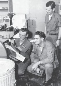 Everett Vanover is shown teaching two of his on job training men how to operate a model 1250 multilith press during the Korean War, 1951. The sergeant who is standing went to school with Elvis Presley.