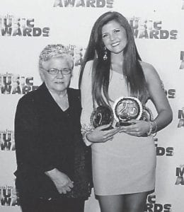 Taylyn Combs was named female entertainer of the year, female vocalist of the year, and songwriter of the year in the category of ages 17-20, at the Georgia Country Gospel Music Awards/Tennessee County Gospel Music Awards held in Nashville, Tenn., at the Country Music Hall of Fame. She now moves on to nationals where she will perform in Gatlinburg in March. She is a physical therapy student at Southeast Kentucky Community and Technical College and is the daughter of Debbie and Gene Combs of Isom. She performed recently at the Kentucky Horse Park and in Frankfort, and will front for Lynyrd Skynyrd with Logan Hall. She is pictured with her grandmother, Elizabeth Couch of Hazard.
