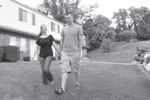 Marine Sgt. Ron Strang, right, walked recently with his girlfriend, Monica Michna, in the yard by his home near Pittsburgh. In 2008, the federal government created AFIRM, the Armed Forces Institute of Regenerative Medicine, a network of top hospitals and universities around the country, and gave $300 million in grants to spur new treatments using cell science and advanced plastic surgery. Strang is among those benefiting. (AP Photo)