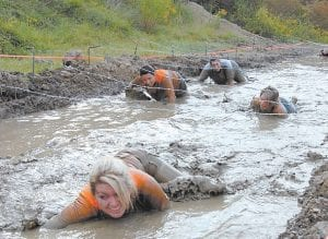 — Brandy Hammonds, Tanya Wright, Terri Thomas and Angie Smith had to stay low to avoid barbed wire while crawling in a mud pit built in West Whitesburg for the first Mountain Mudder competition. The event was held September 22. Organizers hope to make it an annual event during the Mountain Heritage Festival.