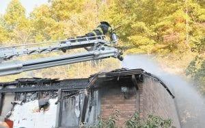 Jenkins Volunteer firefighter Matthew Corbett sprayed hotspots several hours after a fire took the life Dennis Profitt at a Burdine apartment complex. (Photo by Chris Anderson)