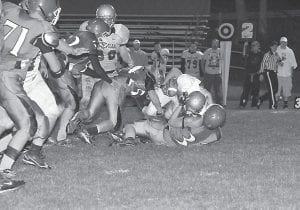 A late-game Pineville rushing attempt was stopped cold as Jenkins teammates Cole Brown, left, and Josh Puckett, bottom, teamed up to take down the ballcarrier in the Cavaliers' 52-0 loss last Friday. Pineville improved to 4-3. The Cavaliers fell to 4-3 and will try to get back on the winning track this Thursday when they visit Hazard for a 7:30 p.m. game. The Bulldogs (3-3) are coming off a 56-19 win over Harlan last week. (Photo by Chris Anderson)