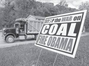 """A truck passed a political sign in a yard in Dellslow, W.Va., last week. Rhetoric about the administration's alleged """"war on coal"""" has come to dominate conversation this campaign season. Once, coal miners were literally at war with their employers. Today, their descendants are allies in a rhetorical war playing out across eastern Kentucky, southwestern Virginia and all of West Virginia. The message: They now face a common enemy — the federal government, especially the president and the Environmental Protection Agency. (AP)"""