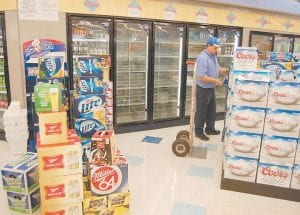 STOCKING THE SHELVES — Shawn Blackburn, a merchandiser with Clark Distributing of Betsy Layne, has been stocking store shelves with beer in the City of Whitesburg since legal sales began October 19. When this photograph was taken on Tuesday, Blackburn was delivering beer to Rite Aid Pharmacy, the first retail outlet to receive a license to sell beer under the city's expanded alcohol ordinance.