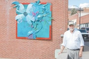 Letcher County artist Doug Adams posed for a photo late last week next to an eightby eight foot art piece he created as part of the Whitesburg streetscape project. This piece depicts spring, and three more pieces will be hung next to it representing the other three seasons.