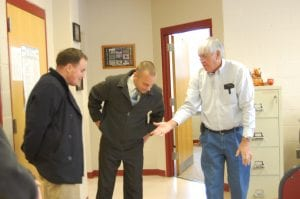 Tom Sexton (left), Matthew Thomas Butler and Letcher Court Clerk Winston Meade looked at the coin Meade tossed which determined who will serve on the Whitesburg City Council. Sexton and Butler each received 282 votes. Sexton won the coin toss. (Photo by Sally Barto)