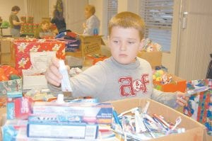 Justin Polly, 9, of Craft's Colly, was busy putting toothpaste and toothbrushes in boxes at the First Baptist Church in Whitesburg on Monday, the first day organizers began collecting gift-filled shoeboxes to be delivered to needy children worldwide through Operation Christmas Child, a project of Samaritan's Purse headed by Franklin Graham. In addition to donating gift-filled shoeboxes, some people donate items including toiletries, socks, small dolls, mittens and hats for volunteers to place those items into shoeboxes. This is the fourth year Justin has volunteered with Operation Christmas Child. The church is located at 170 Madison Avenue in Whitesburg, where shoeboxes may be dropped off from 4 until 8 p.m., November 14-16. On November 17, shoeboxes will be collected from 1-6 p.m. and from noon until 8 p.m. on November 19. (Eagle photo)