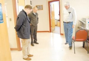 """ALL EYES ON THE PRIZE — The eyes of Whitesburg City Council candidates Thomas Sexton (left) and Matt Butler (center) and Letcher County Clerk Winston Meade were focused on a coin tossed last Thursday to break a tie vote for the sixth council seat. Sexton won the toss by calling """"tails."""" (Photo by Sally Barto)"""