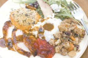 A Thanksgiving dinner plate of cider brined turkey with sage gravy, peach cranberry sauce, sour cream and chive mashed potatoes, sausage pecan stuffing, arugula pear salad with pomegranate vinaigrette and goat cheese and herb crusted sweet potatoes is shown. (AP Photo/Matthew Mead)