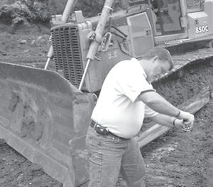 Mike Hansel, father of Kelli Haywood, checks PCB levels at a reclaimed mine site in Letcher County. Hansel, a 1973 graduate of Whitesburg High School who has worked in the coal industry for many years, believes the region's future depends on coal. (Photo by Kelli Haywood)