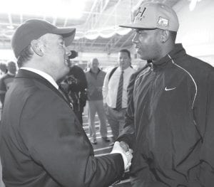 Mark Stoops, newly-named Kentucky football head coach, left, was greeted by former Kentucky quarterback Shane Boyd after a news conference at the Nutter Field House on campus in Lexington. Stoops, the former Florida State defensive coordinator, received a 5-year, $11 million deal. He'll begin his work at Kentucky immediately and will not accompany the Seminoles to their NCAA college football bowl game. (AP Photo)