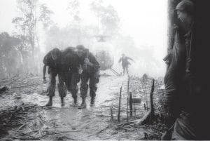 In this May 1969 file photo, a wounded U.S. paratrooper of the 101st Airborne Division based in Fort Campbell, Ky., is helped through a blinding rainstorm by two medics after being evacuated from Dong Ap Bia during the 10-day battle for Hamburger Hill. The Vietnam Veterans of America have joined a class action lawsuit against the armed forces, Their demand: upgrade the veterans' discharges so that they qualify for benefi ts and the medical coverage they deserve.. (AP Photo/Hugh Van Es)