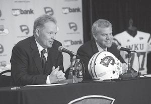 "New Western Kentucky head coach Bobby Petrino, left, responded to a question as athletic director Todd Stewart smiled during a news conference in Bowling Green. The 51-year-old was fired by Arkansas in April for a ""pattern of misleading"" behavior after an accident in which the coach was injured while riding a motorcycle with his mistress as a passenger but now wants to make the most of his second chance. (AP Photo/The Daily News, Joe Imel)"