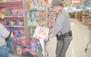 COPS SHOP WITH KIDS — Kentucky State Police Trooper Justin Cornett pushed a cart full of toys during the Shop with a Trooper event held at Walmart here December 7. Eighty-three children in the KSP Post 13 area shopped with troopers, dispatchers, detectives, Walmart employees, local politicians and community volunteers. About $125 was spent on each child.