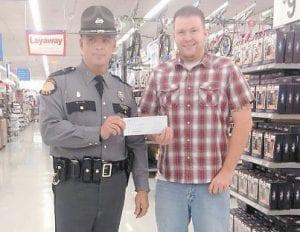 DONATING TO THE CAUSE — At the Shop with a Trooper event at Whitesburg Walmart, Lee Michael Caudill presented a check to KSP Trooper Clayton Stamper for $1,700, which was 100 percent of the profit from the Mountain Heritage truck show. Each year Caudill donates all of the money raised from that event to Shop with a Trooper.