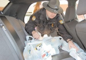 "— Kentucky State Police Trooper Tony Watts loaded a portion of the 2,265 pounds of donated nonperishable food items collected by Mountain Comprehensive Health Corporation in Whitesburg for the KSP's ""Cram the Cruiser"" food drive. A portion of the food was delivered to the Letcher County Food Pantry."