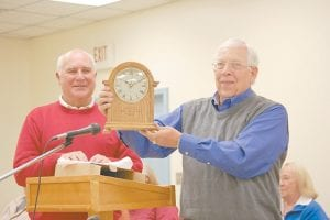 Outgoing Letcher County Board of Education Member John Spicer held up a clock he received for his service to the board as fellow board member Sam Quillen Jr. looked on.