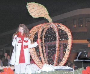 Taylyn Combs sang Christmas music while holding onto a large red apple that was part of a Mountain Comprehensive Health Corporation parade entry that finished third in the best float competition.
