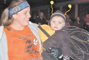 Emily Johnson held her daughter, Evie, who was dressed as a Whitesburg Yellowjacket. Mascots from all Letcher County schools walked in the parade to promote the school-based clinics being offered by Mountain Comprehensive Health Corporation of Whitesburg.