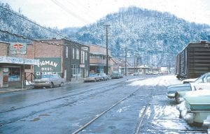 Former Whitesburg Appalachian Regional Hospital physician John Engle snapped this photograph when he was living and working in Whitesburg in the winter of 1964. Pictured is the west end of Main Street formerly known as Railroad Street before the CSX Corp. pulled out the old L&N tracks. Beginning is the old East End Market grocery, Pigman Brothers Dry Cleaners, Auto Parts Inc., KYVA Motor Co., and the Suburban Motel. The structure seen in the distance above the Suburban was the screen belonging to the old Elinda Ann Drive-Inn Theater that was located where Dairy Queen and the Letcher County Recreation Center now sit. The boxcars on the right were in front of the former Lewis Wholesale Building, which now serves as Whitesburg City Hall. We thank Dr. Engle for leaving a copy of the photo with us during a visit this past June. (Photo courtesy John Engle)