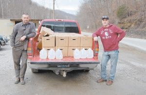 — After reading news reports about undrinkable water at Mill Branch at Deane, Kenny Anderson (left) donated 180 gallons of drinking water to families who live in the area. Anderson and Chris Yonts (right), who has been active in trying to get clean water to the area, delivered the donated jugs last week.