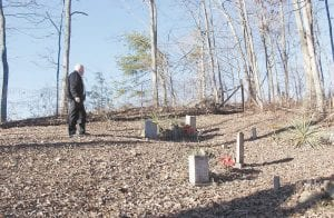 — Carcassonne resident Michael Caudill looked over the Caudill-Hall Cemetery next to his property near Civil War Gap on Monday. Caudill and his wife, Marcia, plan on being buried someday just behind where he is standing in the photo and don't want the cemetery moved as planned.