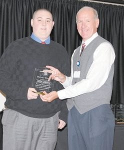 Austin Johnson receives his award from Food City president and CEO Steve Smith.