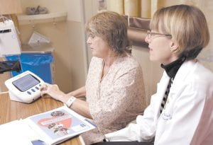 Adult nurse practitioner Jayne Mitchell watched at right as patient Marlena Bechtel- Rysdam, from Elgin, Ore., practiced using an electronic monitoring device called a Health Buddy, at Oregon Health Sciences University in Portland, Ore. (AP Photo)