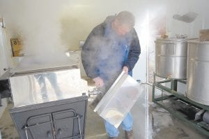 Shad Baker, agriculture agent for Letcher County, poured sap out of a maple syrup evaporator at the Letcher County Extension Office on Feb. 20. Baker said cooking down maple syrup is a learning process.