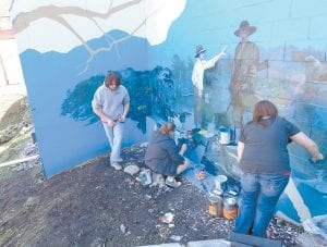 Students who study art under Doug Adams at Letcher County Central High School were photographed by Dr. David Narramore in September while painting on the mural overlooking Main Street.
