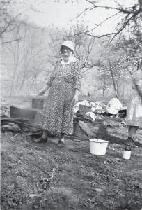 WASHING WITHOUT MACHINES — This photo taken on a washday in the early 1940s shows Louemma Dyer, center, and one of her daughters carrying out the task of cleaning clothes without the modern appliances we all know today. Mrs. Dyer was the grandmother of Bill Marshall, husband of Elva Pridemore Marshall, who writes about helping on washday in Letcher County.