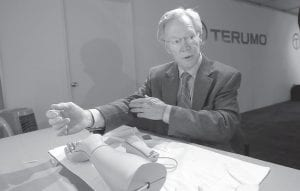 Atlanta cardiologist Dr. Spencer King demonstrated how doctors can open blocked heart arteries by going through an arm, using a model. A Japanese company, Terumo Corp., is one of the leaders of a new way to do it that is easier on patients — through a catheter in the arm rather than the groin. (AP Photo)