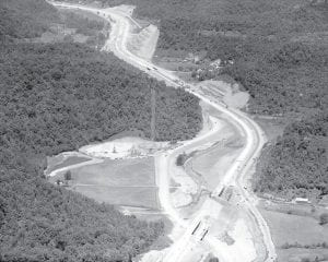THROUGH THE HILLS — This photo provided by state government was taken just a few months before the Eastern Kentucky Turnpike (now known as the Mountain Parkway) was open to public use in March 1963. Visible here in Powell County are the two deepest cuts on the project. The large side-hill cut is in Slade Mountain. Structures visible at lower right were the last two to be completed on the toll road.