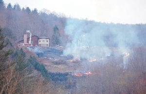 """— Several motorists driving on the Whitesburg bypass Tuesday night thought the Letcher County Extension Office was on fire. It was a false alarm. Extension office employee Mitch Whitaker said he was doing a controlled """"burn off """" on the hillside in front of the building to clear brush so Christmas trees can be planted there later this month. 4-H students and other volunteers will plant about 200 fir trees on the land April 29. The fire was set at 6:30 p.m. Members of the Whitesburg Fire Department were there to help and receive fire training hours. Whitaker said the fire got a little out of hand at one point, but that firefighters were able to keep it under control. (Photo by Sally Barto)"""