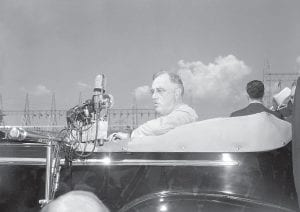 """PROUD OF HIS ACHIEVEMENT — With scoffing reference to critics of the Tennessee Valley Authority, President Franklin D. Roosevelt dedicated the Chickamauga Dam near Chattanooga, Tenn., and the TVA's entire system of dams and resources along the Tennessee River and its tributaries. The President spoke while seated in his automobile at Chickamauga on September 2, 1940, calling the TVA """"one of the great social and economic achievements of our time."""" (AP Photo)"""