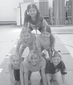Jessie Hicks forms a pyramid with some of her students who attended the Flippin' Out Gymnastics spring camp April 3 at Whitesburg Elementary School. Pictured are (left to right, bottom) Mia Rouse, Jessie Hicks, Ashton Caldwell, (second level) Hailey Frazier, Taylor Banks, and (top level) Emily Banks.