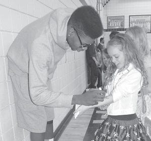 """Kaci McCown, a fourth grade student at West Whitesburg Elementary School, was all smiles last Friday when Nerlens Noel, a UK power forward predicted by many to be the No. 1 pick when the NBA holds its professional basketball draft this summer, autographed her arm after addressing students in the Whitesburg Middle School Gymnasium. In a question and answer session April 23 with Louisville Courier-Journal sports reporter Kyle Tucker, Noel, who has become known for his kindness to children, said """"it wasn't too long ago when I was one of these little kids that looked up to somebody as a role model. When I would see someone that I looked up to, maybe I would've wanted him to say hi to me or come to visit me. That's the way I look at it. You try to give back to kids who aren't as fortunate as myself."""" (Photo by Sally Barto)"""