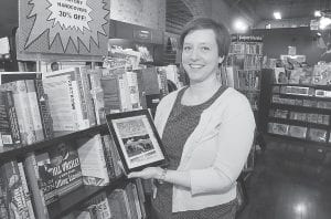 """Romance novelist Susan Maguire displays her book """"Kentucky Home"""" in a bookstore in Charleston, W.Va. It's a classic tale of a double life: mild-mannered librarian by day, steamy romance writer by night. (AP Photo/Charleston Gazette, Chip Ellis)"""