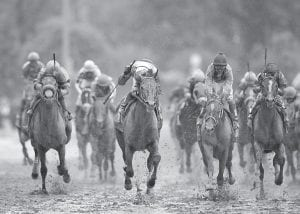 """ORB GETS THE ROSES — Jockey Joel Rosario (center) celebrates after guiding Orb to victory in the 139th running of the Kentucky Derby at Churchill Downs in Louisville on May 5. Goldencents, known as """"Rick Pitino's horse,"""" entered the race as one of the favorites but finished far back on the muddy track. (AP photo)"""